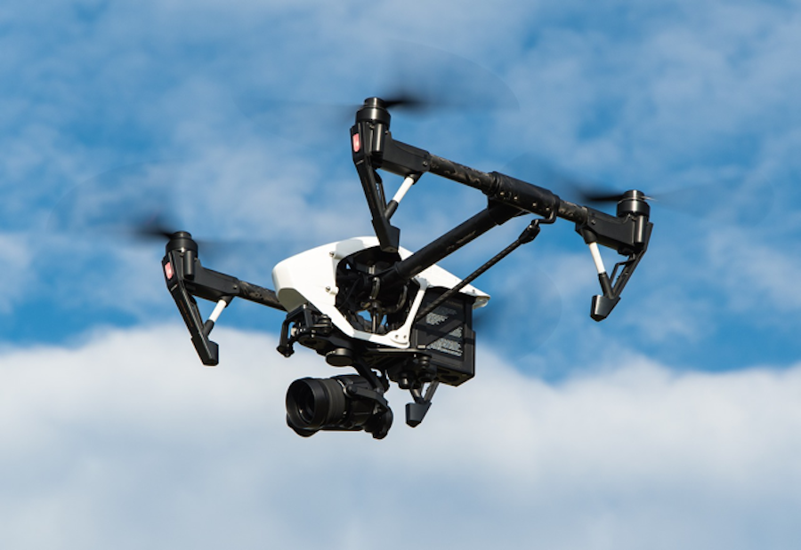 Drone flying with a security camera attached to the bottom