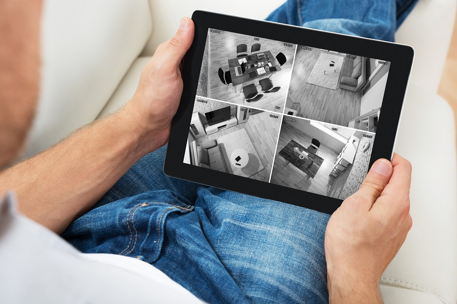 Man Sitting On Sofa While Monitoring Video Footage on a Tablet
