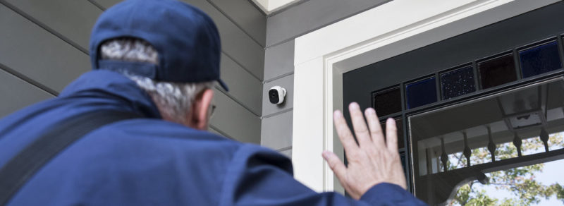 delivery man walking to a front door and waving to a outdoor home security camera